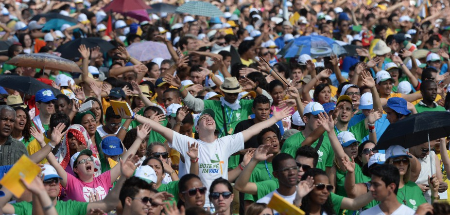 Catholic pilgrims attending World Youth Day (WYD) follow a performer as they wait for the arrival of Pope Francis for the final mass of his visit to Brazil, at Copacabana beach in Rio de Janeiro on July 28, 2013.   (YASUYOSHI CHIBA/AFP/Getty Images