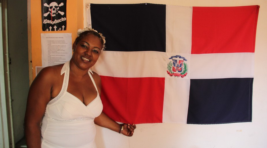 Photo 2: Dominican immigrant Altagracia Pablo poses with her flag. She left dire poverty and immigrated to Puerto Rico 10 years ago. (Photo: Marlon Bishop)