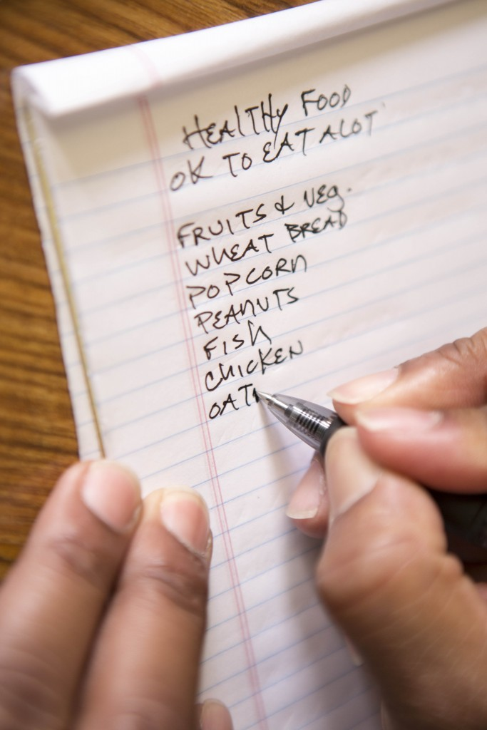 An inmate at San Quentin performs an exercise during the diabetes education class by writing down healthy foods for them to eat.
