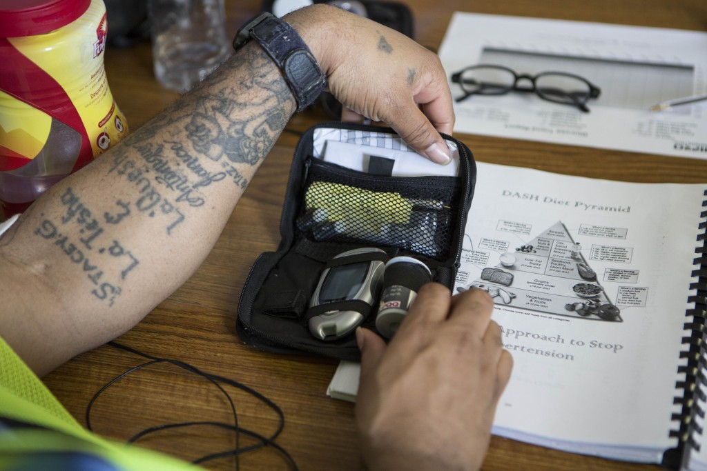 A class participant puts away his blood glucose monitor next to a handout of the food pyramid during a diabetes education class at San Quentin Prison.