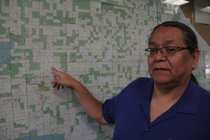 "Tribal government member Matthew Tomaskin points to a map of the reservation. The Yakama have what is called a ""checkerboard reservation"", in which much of the land is actually owned by whites and other non-tribal members."