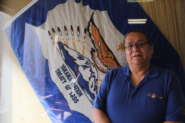 Matthew Tomaskin, legislative liaison for the Yakama Nation tribal government, poses with a Yakama Nation flag at the tribal government building.