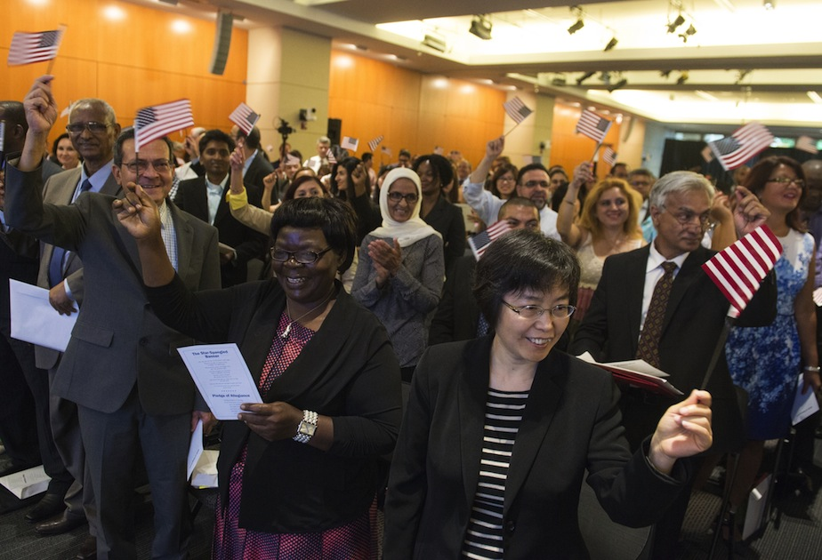People celebrate after taking the citizenship oath to become US citizens during a naturalization ceremony at the US Patent and Trademark Office in Alexandria, Virginia, May 28, 2015. AFP PHOTO / SAUL LOEB        (Photo credit should read SAUL LOEB/AFP/Getty Images)