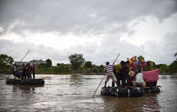 Migrants use a makeshift raft to cross the Suchiate river, natural border between Mexico and Guatemala, in Ciudad Hidalgo, Chiapas state, Mexico on August 31, 2014. Migrants use rafts on their way to the United States. AFP PHOTO/ Yuri CORTEZ        (Photo credit should read YURI CORTEZ/AFP/Getty Images)