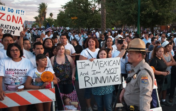 As protestors gather around the Arizona State Capitol against the State Senate bill 1070 May 1, 2010, at sunset, protestor Susan Peralta waves her sign next to a Arizona State Trooper in downtown Phoenix.  When asked her position on the immigration bill, she said, she was not going anywhere!    AFP Photo/Paul J. Richards (Photo credit should read PAUL J. RICHARDS/AFP/Getty Images)