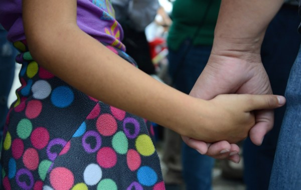 A woman and her daughter hold hands as she speaks to the press upon arriving in San Pedro Sula, about 260 km north of Tegucigalpa, on July 14, 2014 after being deported from the United States. A first group of 120 deportees from Honduras, El Salvador and Guatemala who had crossed into the United States illegally were repatriated by plane to their countries -- most of them unaccompanied youths. US authorities have detained some 57,000 unaccompanied minors since October, twice the number from the same period a year ago, seeking to illegally cross into the US from Mexico.   AFP PHOTO/Orlando SIERRA        (Photo credit should read ORLANDO SIERRA/AFP/Getty Images)