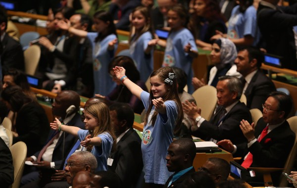"""NEW YORK, NY - APRIL 22:  Children from around the world stand in a procession with world leaders and country delegates in the General Assembly Hall at the United Nations Signing Ceremony for the Paris Agreement climate change accord  on April 22, 2016 in New York City. At least 155 countries are expected to sign the agreement which has the goal of limiting warming to """"well below"""" 2 degrees Celsius above preindustrial levels. The ceremony symbolically takes place on Earth Day.  (Photo by Spencer Platt/Getty Images)"""