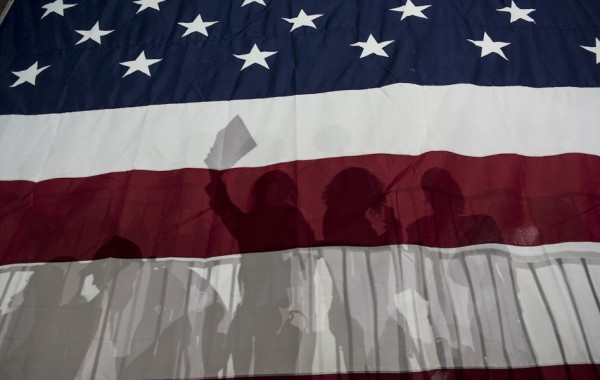 NEW YORK, NY - MARCH 2:  Supporters for Democratic presidential candidate Hillary Clinton are silhouetted in a large American flag at a rally following Super Tuesday on March 2, 2016 in New York City. The former secretary of state won seven states on Tuesday, giving her a lead in the democratic primary.(Photo by Andrew Renneisen/Getty Images)