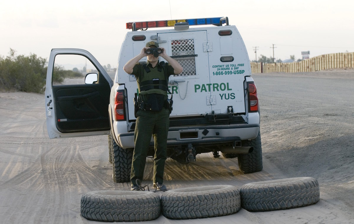 SAN LUIS, AZ - JUNE 7:  A U.S. Border Patrol agent uses a pair of binoculars as he looks at an apparent illegal immigrant (not shown) try to climb over a 15 foot high border fence which leads to Mexico June 7, 2006 in San Luis, Arizona. When the agent is operating his vehicle, he drags the tires (shown behind his truck) so he can spot new footprints in the sand. The border fence runs for about six miles along the San Luis border, and is being extended about 1,000 yards by members of the Utah National Guard which is part of U.S. President George W. Bush's Operation Jumpstart.  (Photo by Gary Williams/Getty Images)