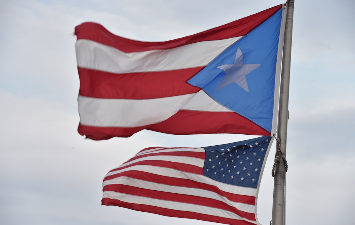 The Puerto Rican and US flags are seen in the Old Town  district  February 9, 2015  in San Juan, Puerto Rico.      AFP PHOTO/PAUL  J. RICHARDS        (Photo credit should read PAUL J. RICHARDS/AFP/Getty Images)