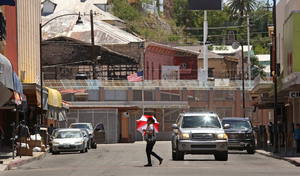 A pedestrian walks across Morley Avenue with the Morley Gate at the international border in the background. The photo was taken on Wednesday, July 8, 2015, in Nogales, Ariz. Photo by A.E. Araiza/ Arizona Daily Star
