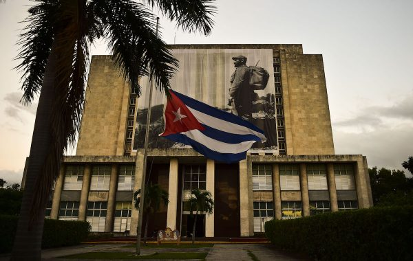 View of the facade of the Cuban national library with the Cuban flag at half mast and a picture of Cuban revolutionary leader Fidel Castro at the Revolution Square in Havana, on November 27, 2016, two days after he died aged 90.  Cuban revolutionary icon Fidel Castro died late November 25 in Havana, his brother, President Raul Castro, announced on national television. Castro's ashes will be buried in the historic southeastern city of Santiago on December 4 after a four-day procession through the country. / AFP / RONALDO SCHEMIDT        (Photo credit should read RONALDO SCHEMIDT/AFP/Getty Images)