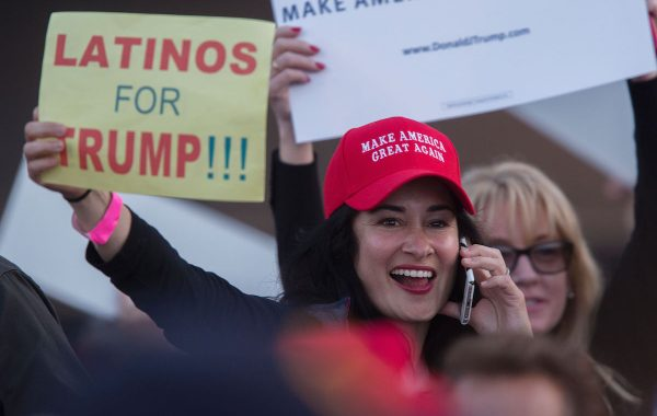 A woman hoods a sign expressing Latino support for Republican presidential candidate Donald Trump at his campaign rally at the Orange County Fair and Event Center, April 28, 2016, in Costa Mesa, California. Trump is vying for votes in the June 7 California primary election in hope of narrowing the gap to the 1,237 delegates needed to win the Republican presidential nomination. / AFP / DAVID MCNEW        (Photo credit should read DAVID MCNEW/AFP/Getty Images)