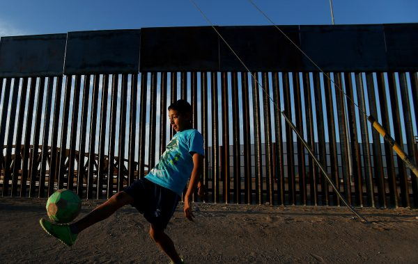 "Joel Mendez (UMLAUT OVER ""O""), 13, juggles a soccer ball in the setting sunlight along Avenida Captain Carlos G. Calles just south of the international border fence in San Luis Rio Colorado, Sonora, Mexico.  Latitude: 32.487203 Longitude: -114.789625  Photo taken Wednesday, April 27, 2016."