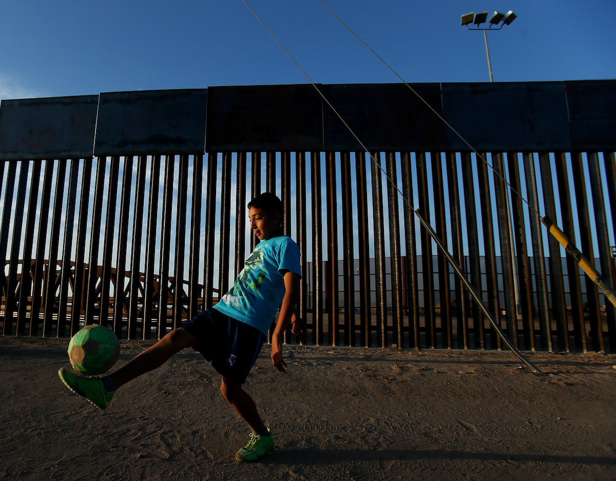 "Joel Mendez (UMLAUT OVER ""O""), 13, juggles a soccer ball in the setting sunlight along Avenida Captain Carlos G. Calles just south of the international border fence in San Luis Rio Colorado, Sonora, Mexico.  Latitude: 32.487203 Longitude: -114.789625  Photo taken Wednesday, April 27, 2016."