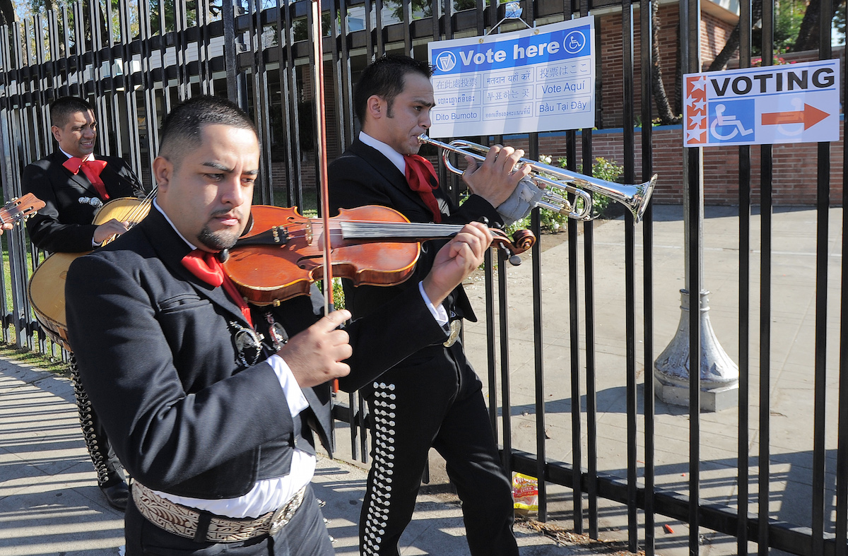 Mariachi musicians sing and play as they go from house to house to encourage people to come to vote on election day at the Sun Valley's Latino district, Los Angeles County, on November 6, 2012 in California.AFP PHOTO /JOE KLAMAR (Photo credit should read JOE KLAMAR/AFP/Getty Images)