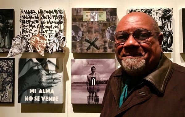 """Puerto Rican artist Juan Sanchez in front of his art piece , """"Economicamento Esclavos"""" (top right). Photo by Nicole Acevedo."""